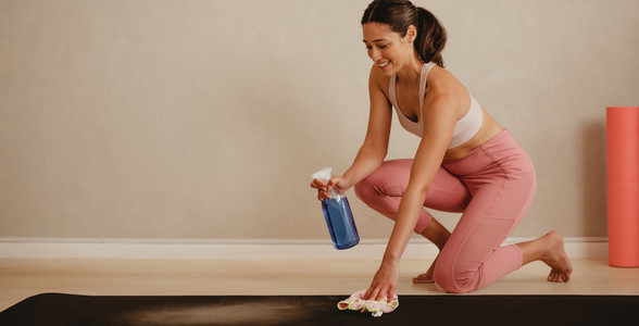 Woman sanitizing yoga mat at fitness studio