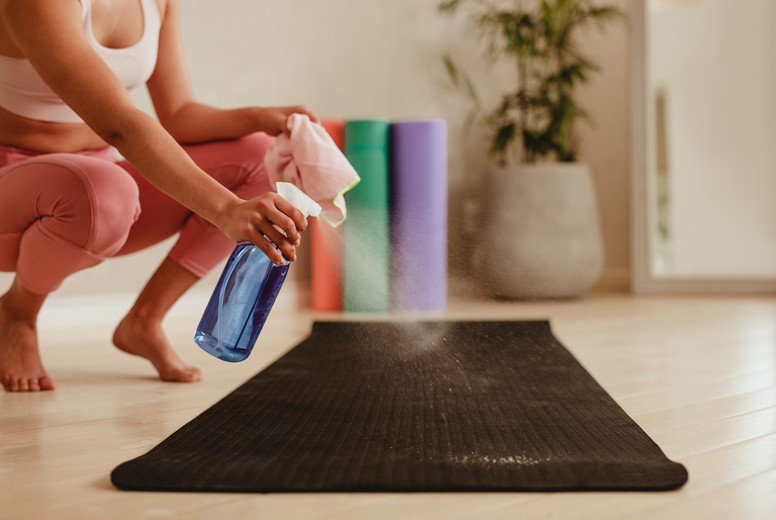 Woman cleaning exercise mat with disinfectant spray in gym