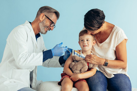 Doctor giving vaccine to a boy