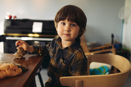Innocent kid sitting at table