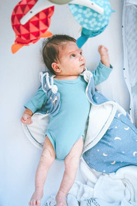 Superhero baby lying down in her bed