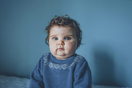 Portrait of a little baby in a blue room