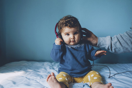 Little baby playing with her daddys headphones