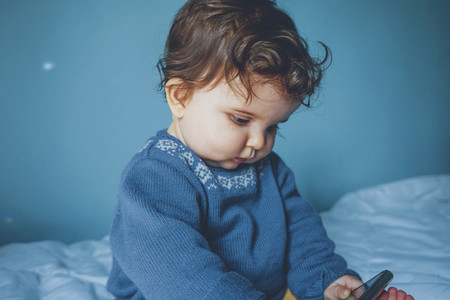 Little baby playing with a smart phone in a blue room