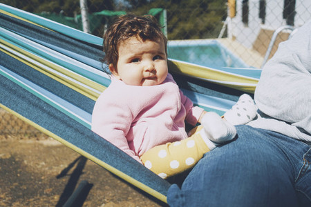 Little baby having fun on a hammock in a sunny day