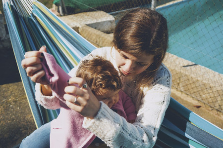 Young woman caring her baby sitting on a hammock