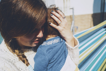 Image about real motherhood of a young mom hugging her baby