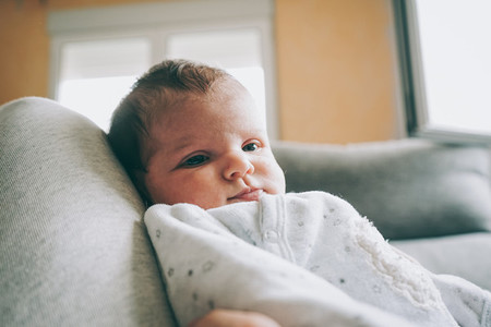 Lovely newborn baby girl with a warm pajama at home