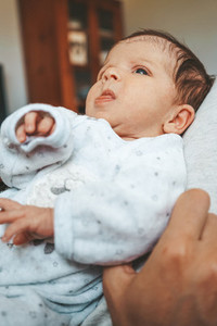 Upset newborn baby in pajama at home
