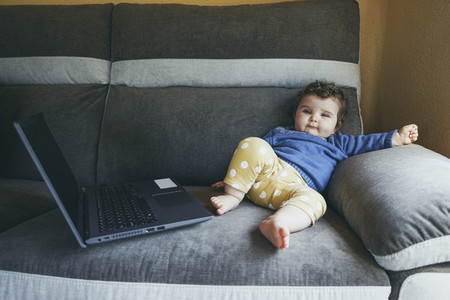 Little baby at home playing with a laptop