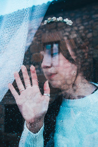 Sad woman alone in her home looking through a window in a rainy
