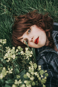 Young beautiful woman resting in a field of flowers