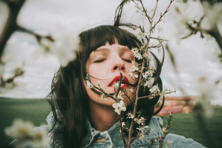 Beautiful young woman posing near spring flowers