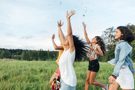 Group of multi ethnic female friends raised hands up and throwing confetti while running on a field