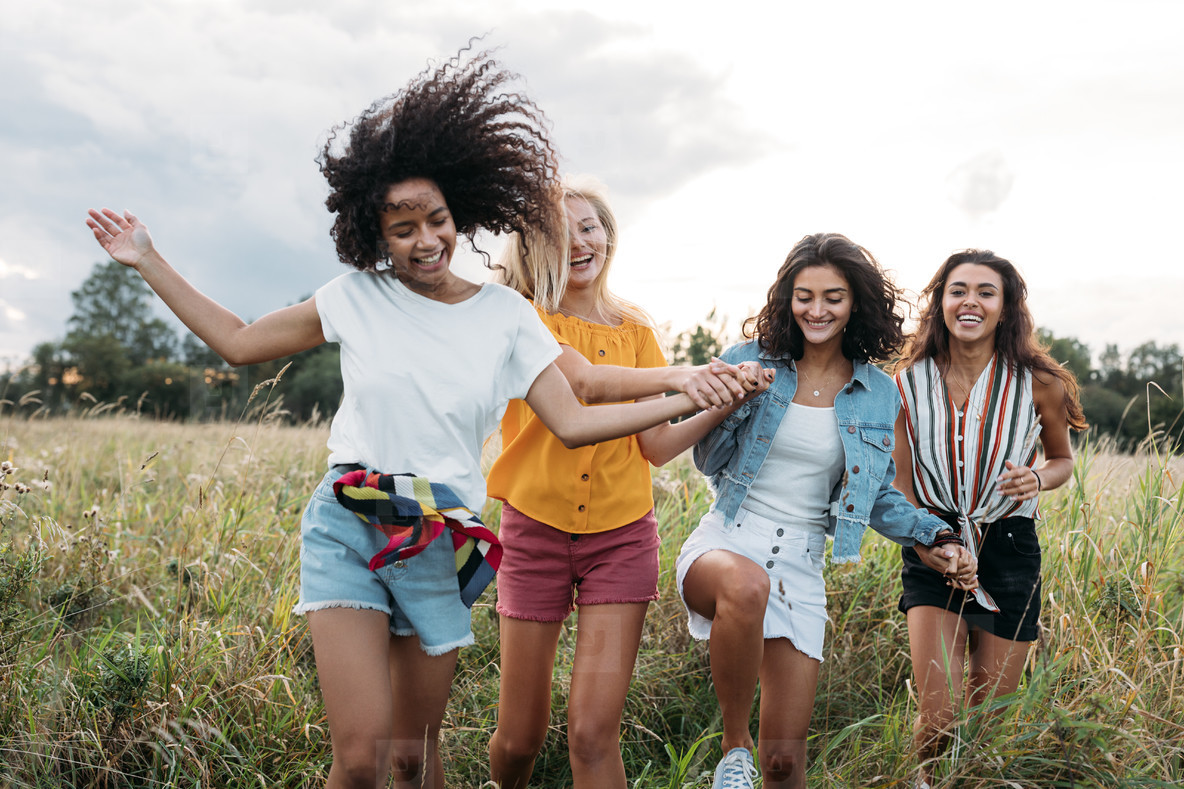 Four happy women hold hands and running on a field  Female friends having good times outdoors
