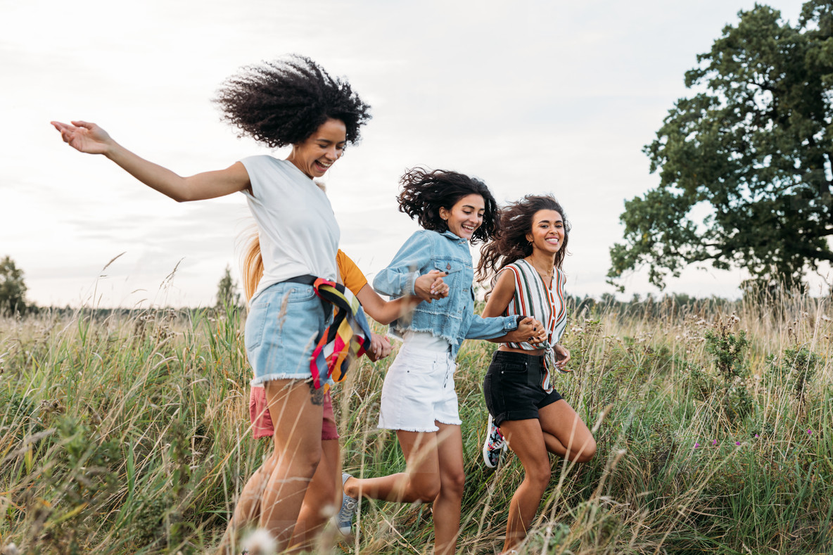 Four women holding hands running on field  Laughing friends having fun outdoors in summer