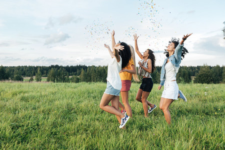 Side view of four female friends running on a field and throwing confetti