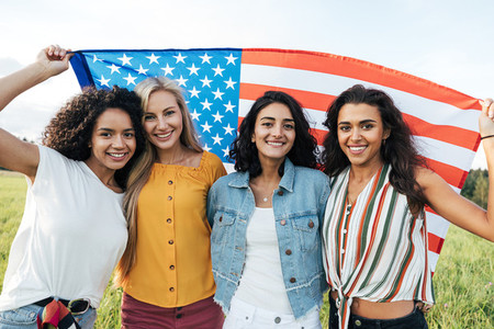 Group of multi ethnic women holding a USA flag  Female friends celebrating independence day