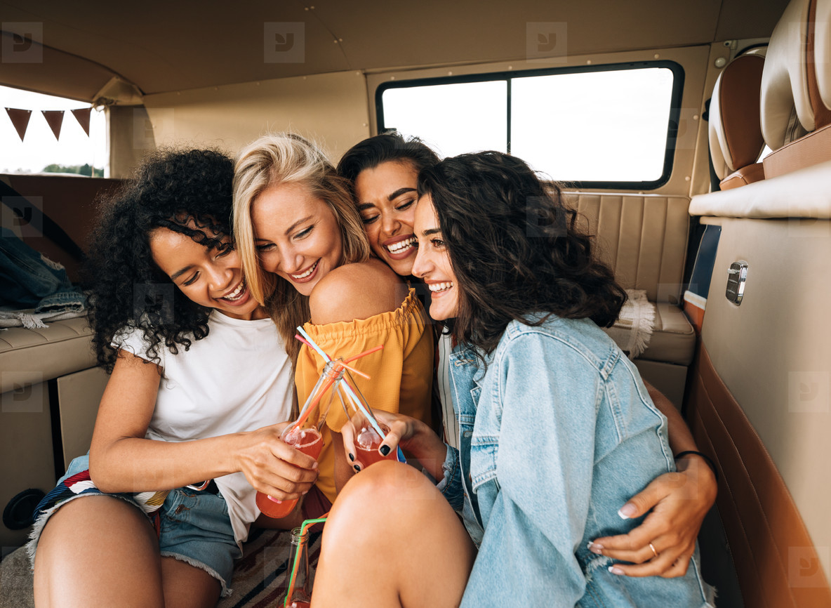 Group of four young women cuddling each other while sitting in van enjoying vacation