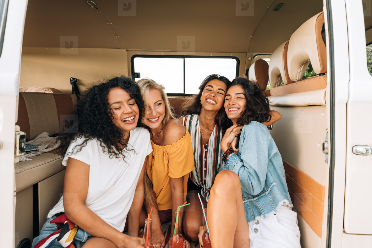 Happy young women sitting together in camper van enjoying vacation