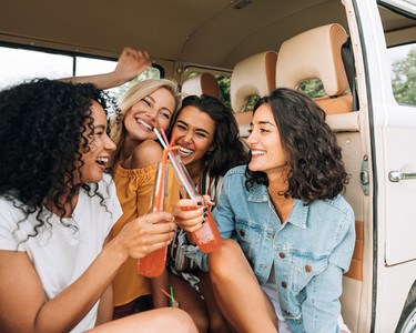 Happy women sitting together in van during road trip  Smiling females having fun and drinking cocktails in car