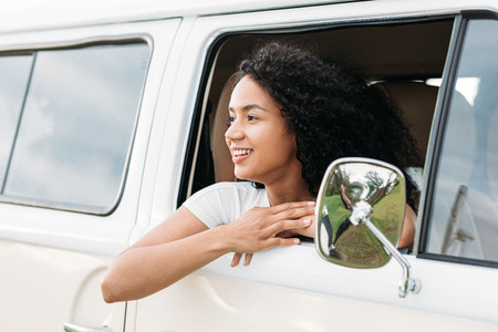Smiling mixed race woman looks out from van window enjoying a road trip