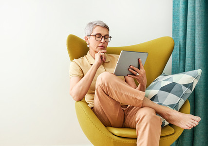 Thoughtful mature woman with closed eyes sitting at home holding a digital tablet