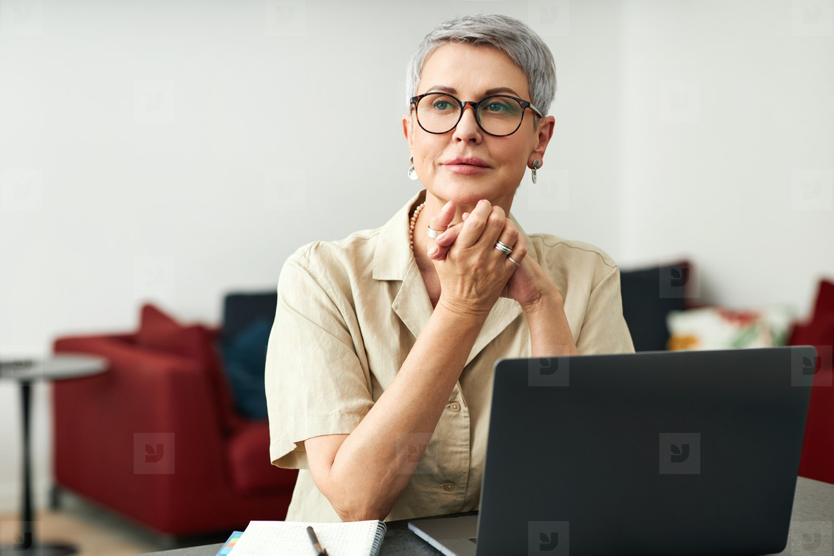 Stylish mature woman with grey hair wearing glasses sitting at home in front of a laptop