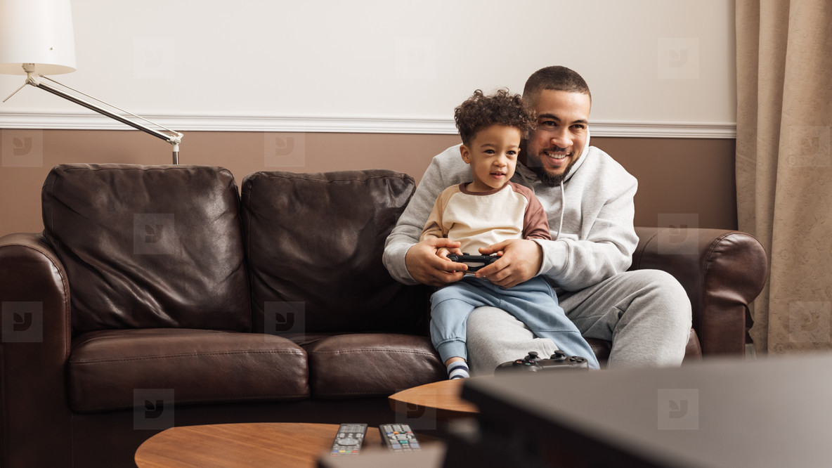 Little boy sitting on the hip of his father and holding joystick  Smiling father and his son playing video games at home