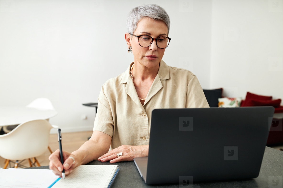 Mature woman looking at laptop screen making notes at home