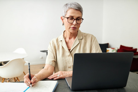 Mature woman looking at laptop screen making notes at home