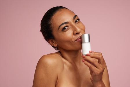 Beautiful woman kissing cosmetic product