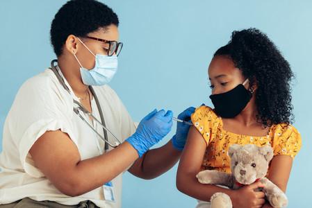 Pediatrician giving vaccine to a girl