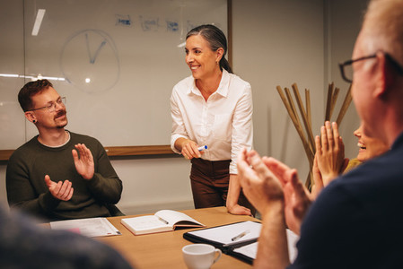 Businesswoman getting applause in team meeting