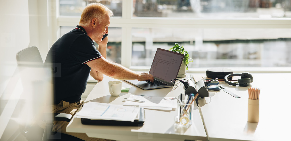 Businessman talking over phone while working on laptop