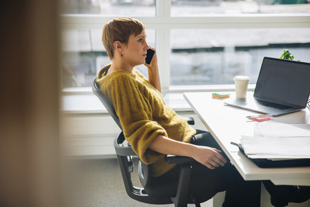 Woman sitting at her desk talking on mobile phone