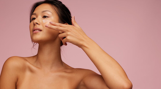 Asian woman applying anti aging cream on her face