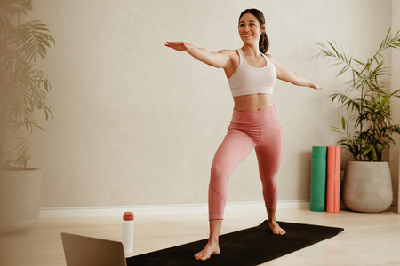 Woman doing yoga at home with laptop in front