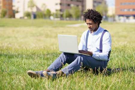 Black man with afro hair using his laptop sitting on skateboard on the grass of an urban park