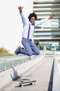 Black businessman jumping on a skateboard near an office building