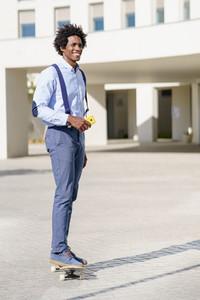 Black businessman on a skateboard holding a smartphone outdoors