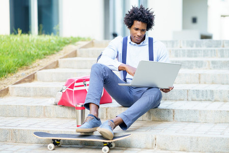 Black businessman with afro hair and skateboard using his laptop computer sitting on some steps