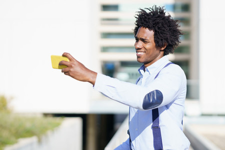 Black businessman taking a selfie with his smartphone near an office building