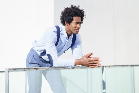 Attractive black businessman with afro hair  resting on a railing of his office building
