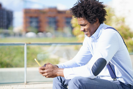 Black man with afro hairstyle using a smartphone sitting near an office building