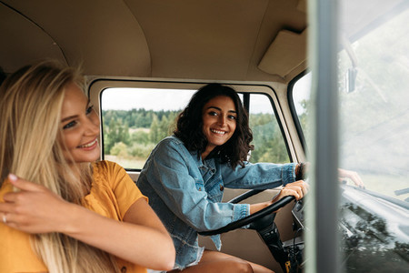 Young woman sitting on a driver seat in camper van  Two women in a car during a road trip