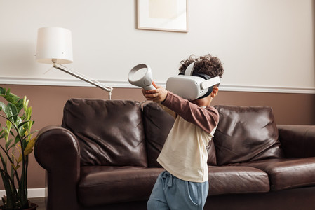 Kid playing virtual reality game in a living room holding joystick with two hands