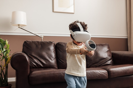 Boy wearing virtual reality headset using controller while exploring cyberspace in living room
