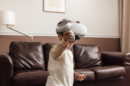 Little smiling boy wearing VR goggles using a controller for interaction in a game