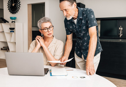 Senior couple with laptop calculating finances in the dining room  Two retired people with documents at home